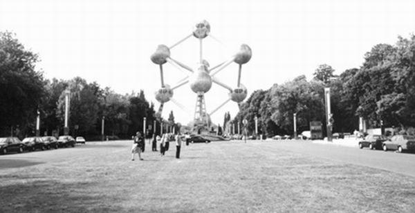 、一亿倍时,它又是个什么模样呢?当我站在按放大近2000亿倍的铁原子所构成的原子球塔面前时,你就完全可以理解我当时心里的激动与震撼了。 原子球塔位于比利时首都布鲁塞尔西北郊的海塞尔高地,是布鲁塞尔十大名胜之一,有比利时的艾菲尔铁塔之美称。那天清晨,当我们踏着晨露,走进树木葱郁、绿草如茵、风景优雅的易明多公园时,远远地我们就看到了在霞光映照下高高耸立的原子球塔。 这是一座造型独特、气势宏伟、令人叹为观止的庞大建筑物。它高约102米,重达2200吨,由九个巨大的不锈钢圆球联贯而成。每个圆球直径约18米,圆球内